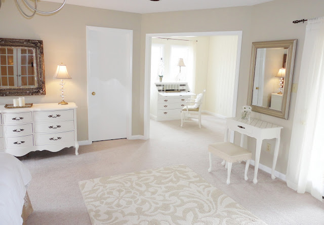 6-2-neo-classical-style-bedroom-interior-design-light-beige-walls-white-furniture-upholstered-dressing-table-ottoman-curved-chest-of-drawers-rug-mirror-adjoining-room