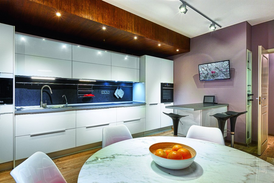 8-wooden-ceiling-decor-in-interior-design-oak-panels-built-in-lights-white-kitchen-cabinets-dining-area-track-lights-marble-round-table-island