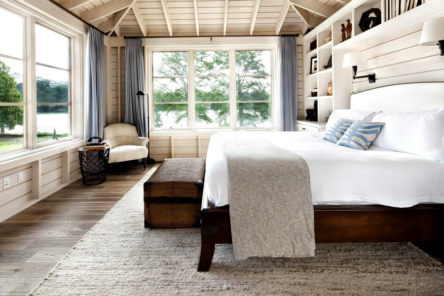 0-beautiful-inspiring-bedroom-interior-design-in-traditional-style-with-river-lake-view-big-windows-beige-wooden-walls-shelving-rug-arm-chair-curtains-lamps-wicker-chest