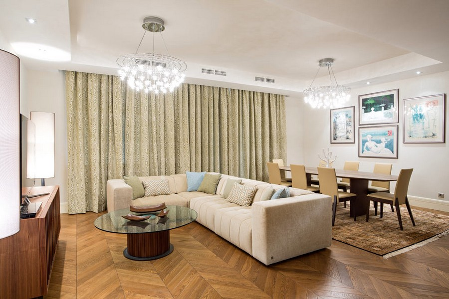 0-light-traditional-style-interior-design-living-room-dining-area-herringbone-oak-parquet-beige-corner-cofa-chandeliers-oval-table-chairs-curtains-glass-coffee-table-wall-art