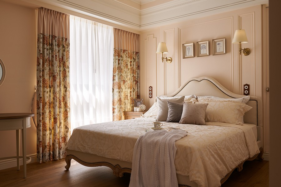 1-1-neo-classical-style-interior-neutral-beige-blue-Tuscan-colors-bedroom-upholstered-bed-with-rivets-wall-panels-moldings-nightstand-wall-lamps-sconces-throw-pillows-floral-curtains
