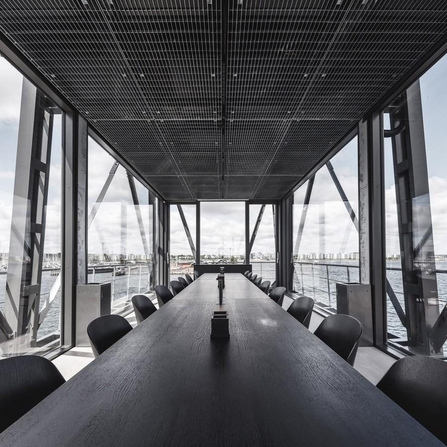 1-3-remade-reconstructed-ex-harbor-crane-apartment-in-Copenhagen-dark-black-graphite-gray-interior-long-negotiation-table-metting-room-conference-hall-panoramic-windows-sea-port-view