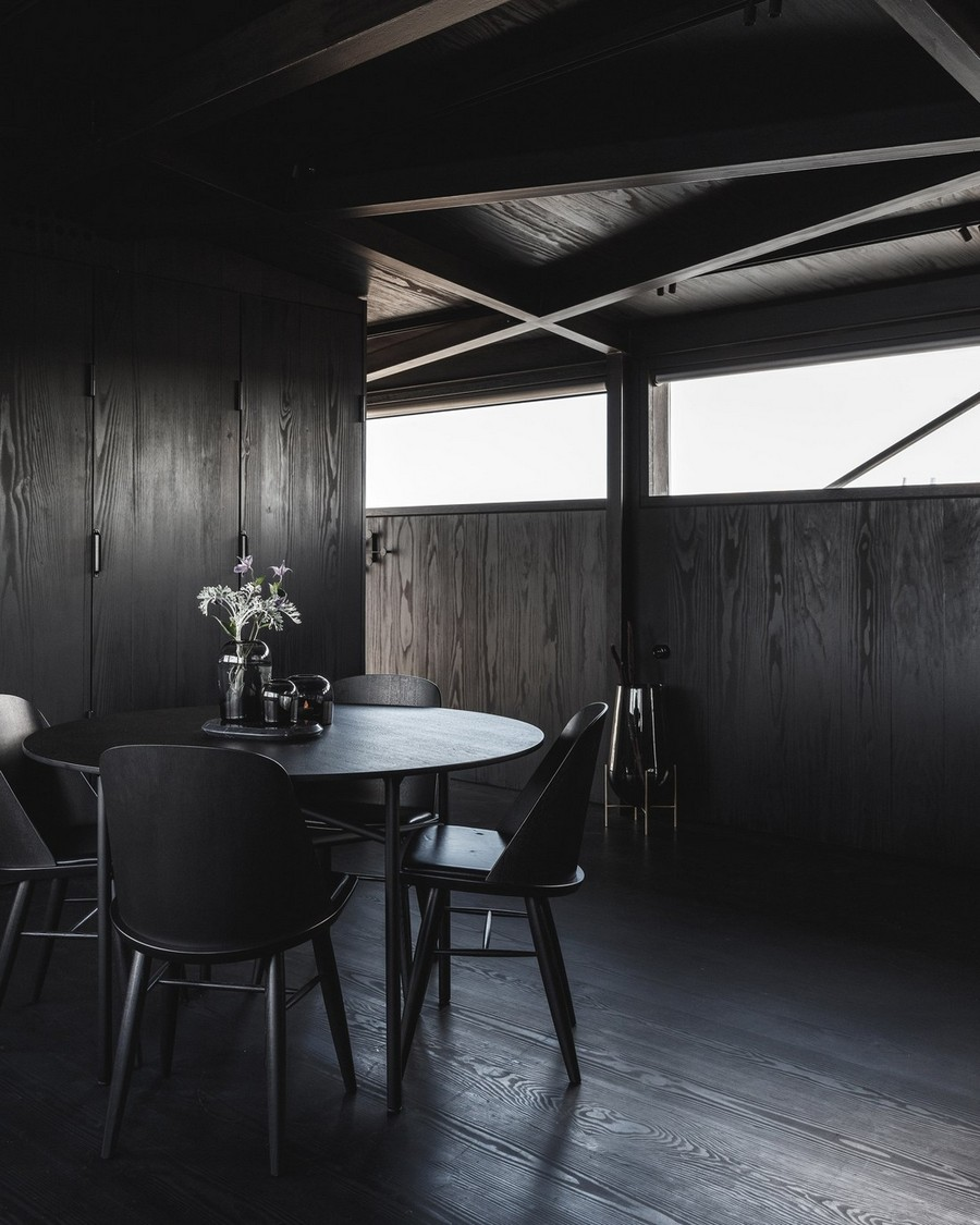 1-7-remade-reconstructed-ex-harbor-crane-apartment-in-Copenhagen-dark-black-graphite-gray-interior-dining-room-area-round-table-wooden-walls-charcoal-wood-chairs