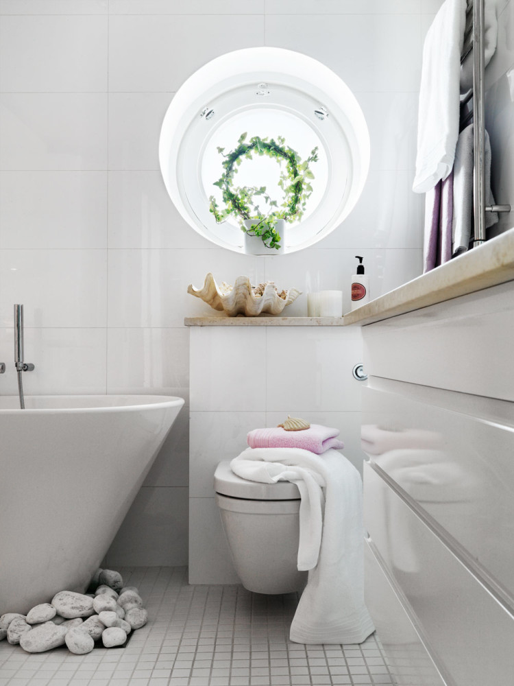 1-contemporary-Scandinavian-eclectic-style-bathroom-interior-design-with-oriental-motifs-bathtub-rocks-pebbles-on-the-floor-white-glossy-square-wall-tiles-small-floor-round-window-indoor-plant-vanity-unit