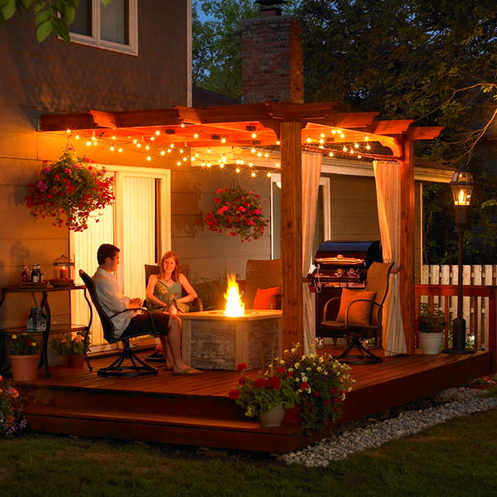 1-family-couple-girl-boy-on-verandah-terrace-summer-night-fire-pit-holiday-lights-garden-lantern-pebbles-arm-chairs-flowers