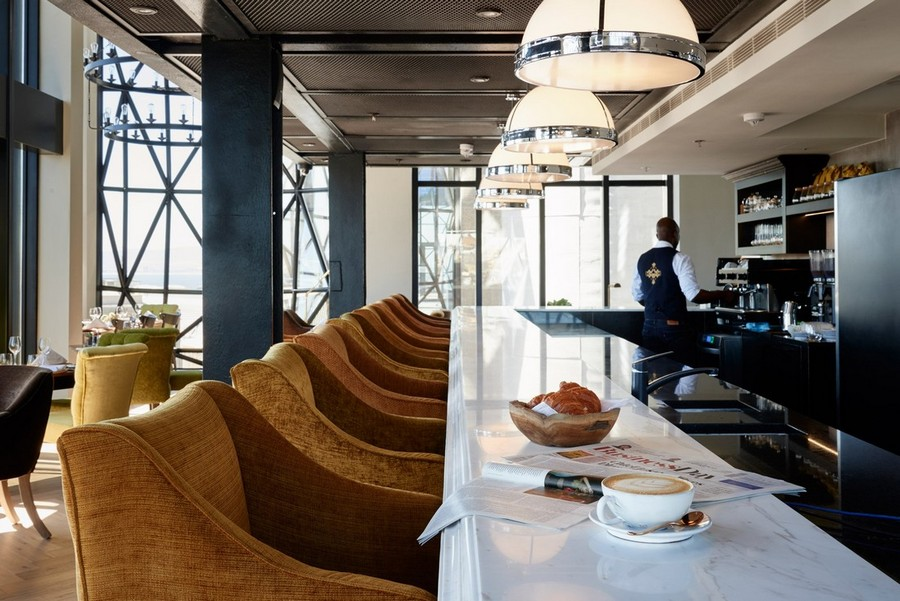 2-5-remade-building-in-South-Africa-Cape-Town-Royal-Portfolio-Hotel-ex-grain-elevator-interior-lobby-bar-five-star-hotel-arm-chair-bar-stools-white-marble-countertop-barman-pendant-lamps