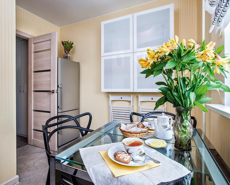4-2-small-kitchen-interior-design-ideas-cabinets-folding-dining-chairs-refrigerator-behind-the-door-roman-blinds-dining-table-black-chairs-yellow-flowers-stripy-wallpaper