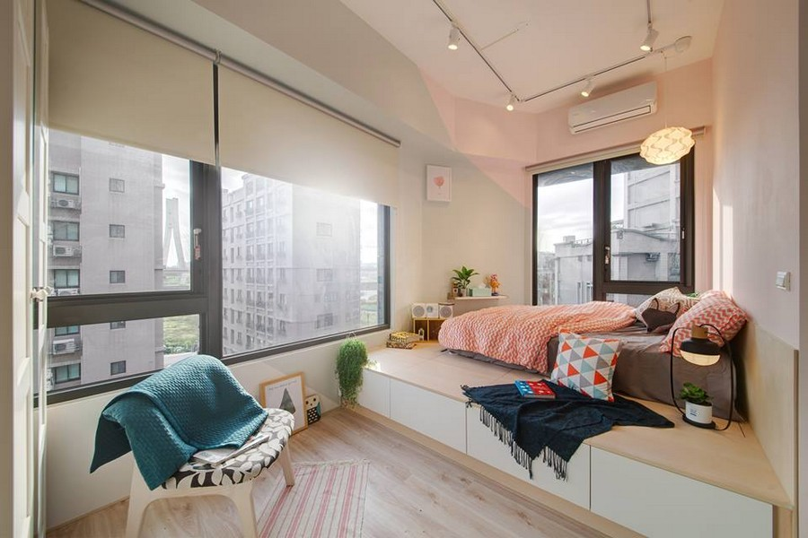 5-3-interior-by-A-Lentil-Design-Taiwan-China-white-walls-light-panoramic-windows-bedroom-bed-on-a-podium-storage-drawers-mattress-blue-and-red-geometric-accents-track-lights-chair-rug