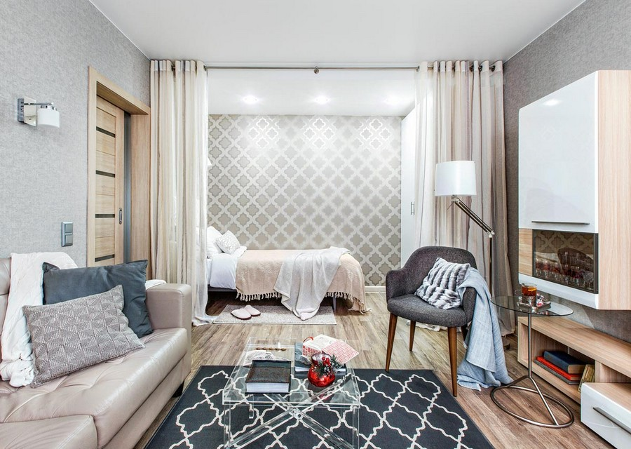 6-one-room-apartment-interior-design-ideas-curtains-room-divider-bed-in-the-living-room-lounge-sleeping-area-beige-curtains-white-cabinets-geometrical-wallpaper-rug-transparent-plastic-coffee-table-sofa