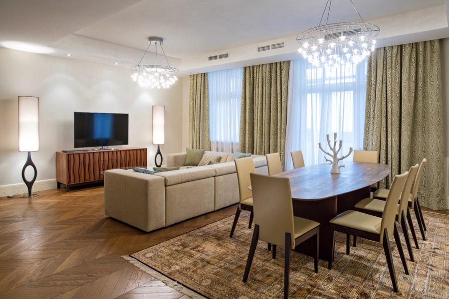 7-light-traditional-style-interior-design-living-room-dining-area-herringbone-oak-parquet-beige-corner-cofa-chandeliers-oval-table-chairs-curtains-floor-lamps-elegant