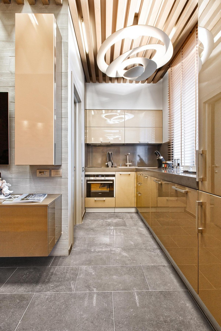 8-1-one-room-apartment-interior-design-ideas-light-brown-glossy-kitchen-cabinets-white-top-cabinets-gray-ceramic-floor-tiles-ceiling-wooden-planks-decor-geometrical-lamp-wall-mounted-TV-rack