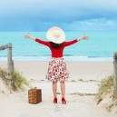 0-leaving-for-holidays-woman-came-to-the-sea-on-vacation-with-a-suitcase-red-shoes-hat-sand-beach-happy