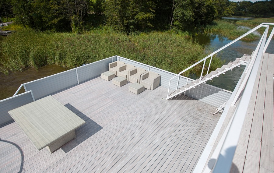 12-houseboat-float-house-exterior-design-in-nautical-style-light-larch-wood-floor-light-low-deck-terrace-table-arm-chairs