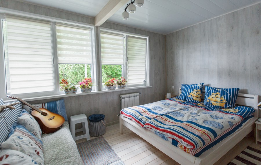 3-houseboat-float-house-interior-design-in-nautical-style-light-laminate-walls-larch-wood-floor-light-blue-red-accents-master-bedroom-wooden-bed-sofa-guitar-stool-rug