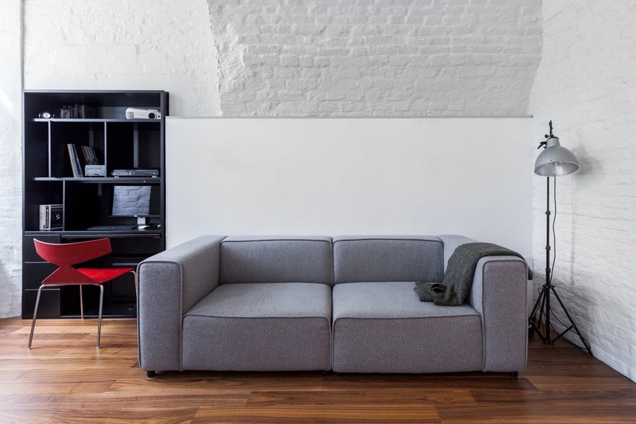 3-minimalist-style-ascetic-interior-painted-white-walls-brick-masonry-arched-ceiling-American-walnut-floor-lamp-gray-sofa-black-shelving-unit-red-chair