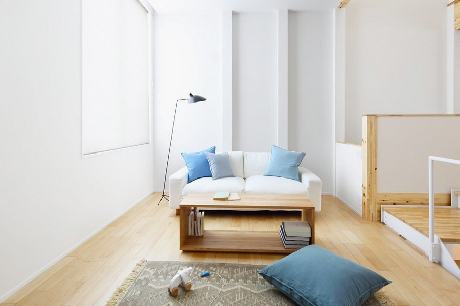 3-minimalist-style-interior-white-walls-light-wood-floor-furniture-Scandinavian-style-living-room-lounge-area-sofa-blue-throw-pillows-rug-floor-lamp