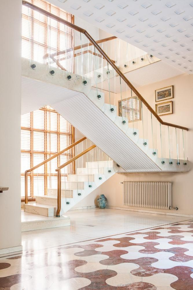 4-Italian-villa-interior-design-by-Osvaldo-Borsani-hallway-entrance-hall-white-marble-and-glass-staircase-luxurious-marble-floor-tiles-geometrical-motifs-panoramic-windows-radiator