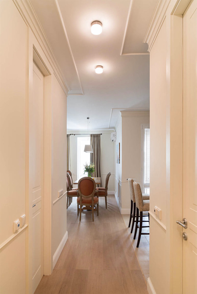 5-1-beige-interior-traditional-style-open-plan-kitchen-dining-room-light-neutral-doors-corridor-hallway-wall-panelling-parquet-floor-upholstered-terracotta-chairs