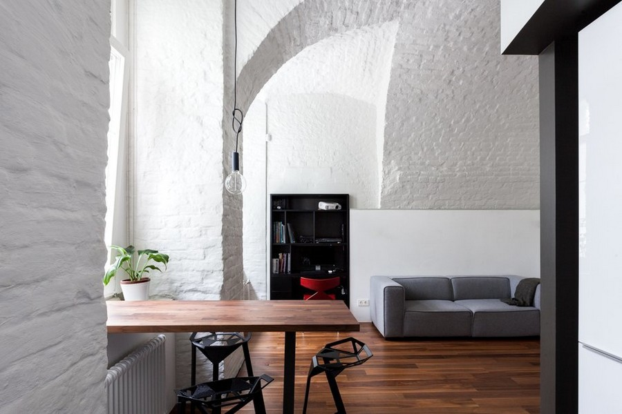 6-minimalist-style-ascetic-interior-painted-white-walls-brick-masonry-arched-ceiling-American-walnut-floor-living-room-open-plan-dining-area-bar-table-stools-gray-sofa-black-shelving-unit-exposed-pendant-bulb