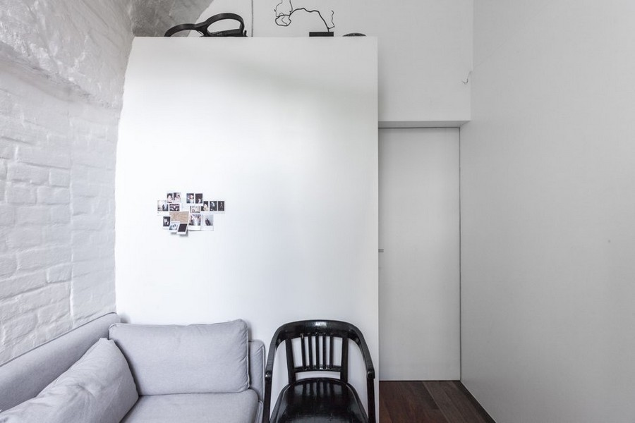 7-minimalist-style-ascetic-interior-painted-white-walls-brick-masonry-arched-ceiling-small-narrow-room-gray-sofa-chair