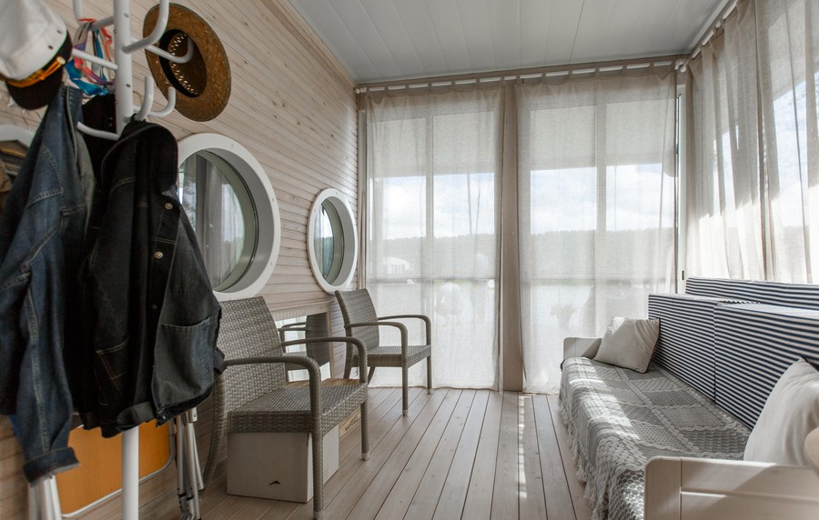 8-houseboat-float-house-interior-design-in-nautical-style-light-laminate-walls-larch-wood-floor-light-blue-accents-lounge-area-living-room-narrow-elongated-sofa-round-windows-chairs-coat-rack