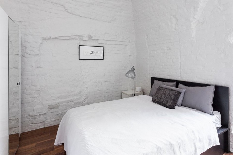 9-minimalist-style-ascetic-interior-painted-white-walls-brick-masonry-arched-ceiling-kid's-room-bedroom-gray-pillow-black-bed-table-lamp-nightstand-picture