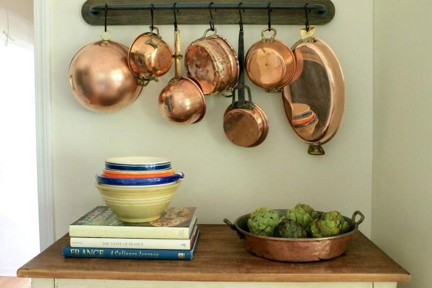 1-copper-in-interior-design-of-kitchen-utensils-on-a-railing-wooden-countertop-basket-saucers-metal