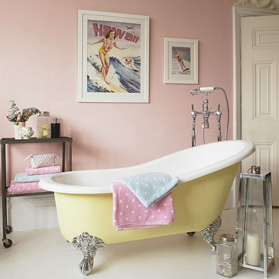 10-vintage-retro-style-bathroom-interior-pastel-pink-painted-walls-free-standing-yellow-claw-foot-bath-bathtub-shower-head-polka-dot-blue-towels-candle-holder-serving-trolley-storage-pin-up-Hawaiian-posters-1950s