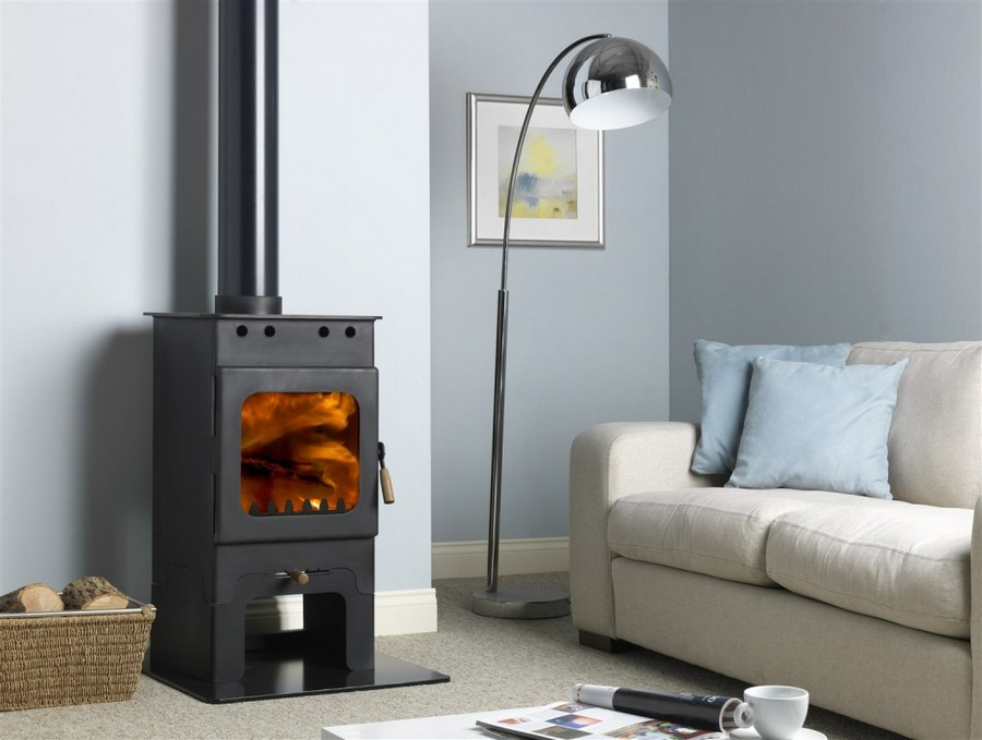 2-Wakerley-cover-plate-oak-wood-burning-stove-in-a-cottage-country-house-living-room-wicker-timber-log-basket-light-grey-sofa-blue-walls-floor-lamp-coffee-table
